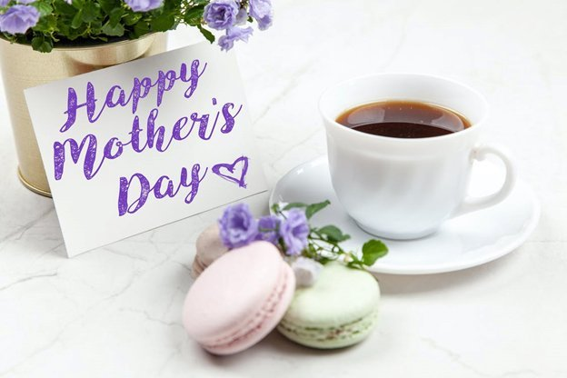 A mother's day card next to a cup of coffee and some macarons