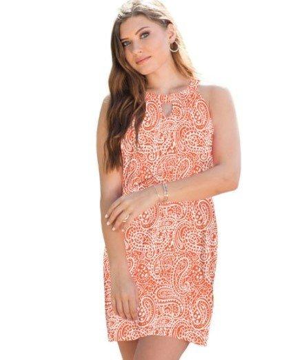 A woman poses in a beautiful orangey-peach halter top sleeveless dress.