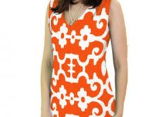 A woman wears a bright, printed dress that flatters her lean physique.